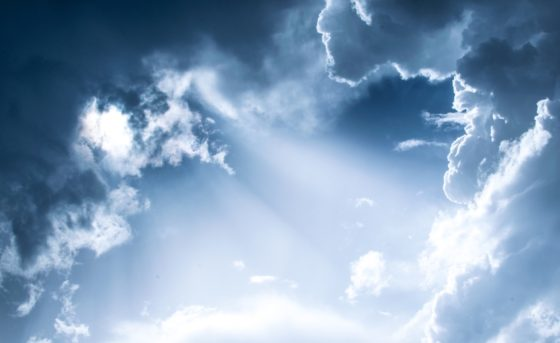 sky view of sunshine breaking between clouds