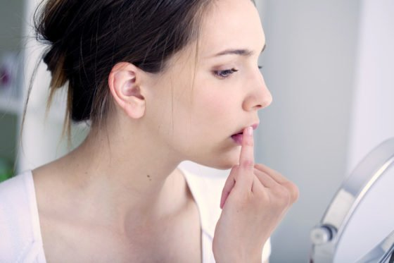 woman checking cold sore on upper lip