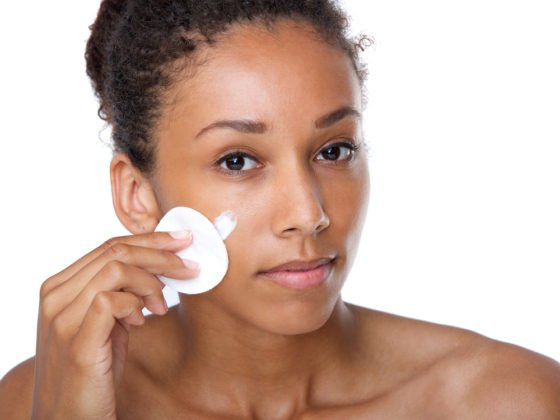 woman applying skincare with cotton round