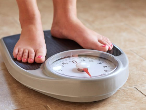 standing on scale to measure weight