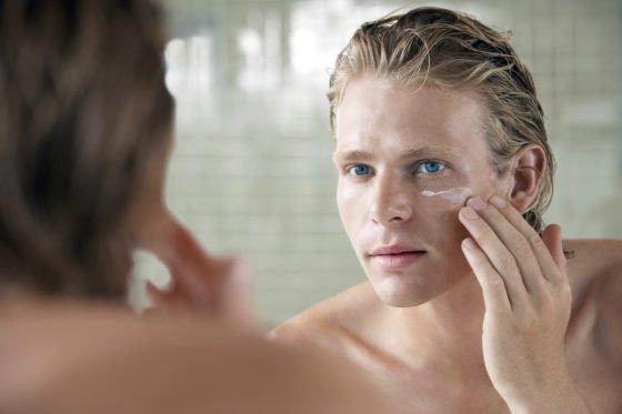 man applying face cream