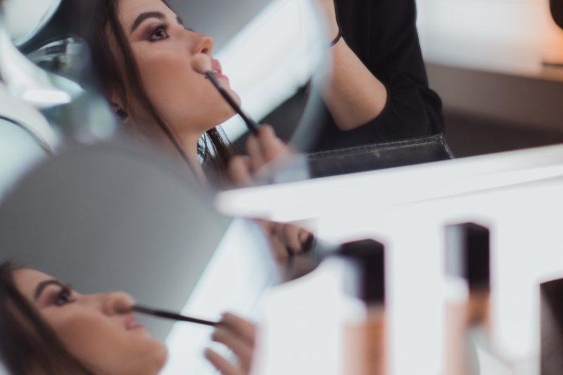 reflection of woman applying makeup